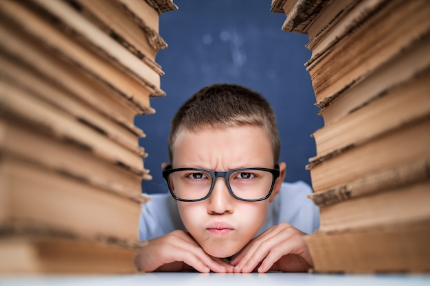 Школьник в очках сидит между двумя стопками книг и смотрит в камеру с надутыми щеками.