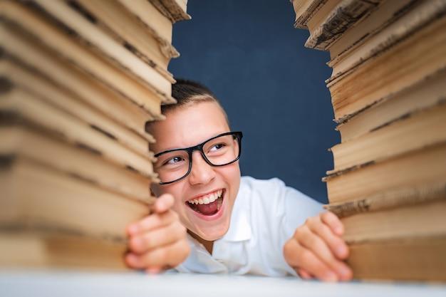 Школьник в очках сидит между двумя стопками книг и улыбается от камеры.