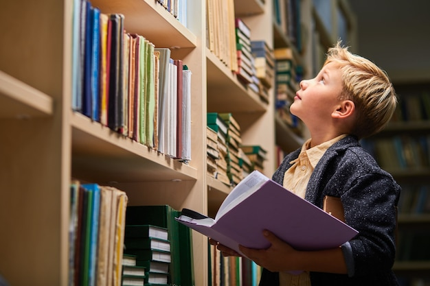 School boy looking up at bookshelves in campus library, child boy holding book in hands