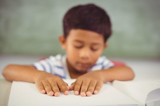 School boy memorizing the lesson in classroom