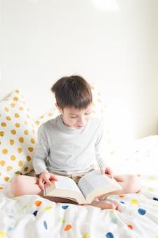 ベッドの上の学校の男の子と家で本を読んで学校の宿題をしています。オンライン教育の遠隔学習。検疫。緊急時に家にいるコンセプト