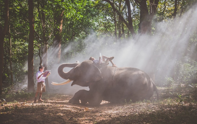 彼の友人の象とジャングルで遊ぶ学校少年