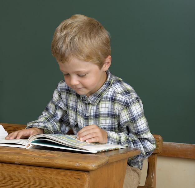 School boy reading in the classroom