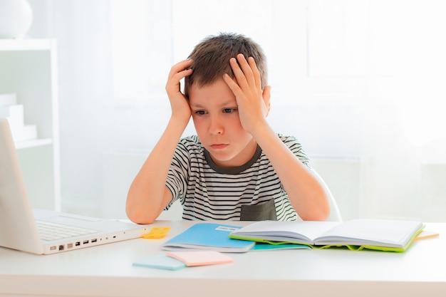 勉強に飽き飽きしている小学生が学習中のエネルギー疲労が不足している本のトレーニング資料でいっぱいの自宅の教室の横になっている机に座っている男子生徒。過労