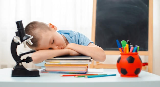 School boy sitting home classroom lying desk filled with books training material schoolchild sleeping lazy bored
