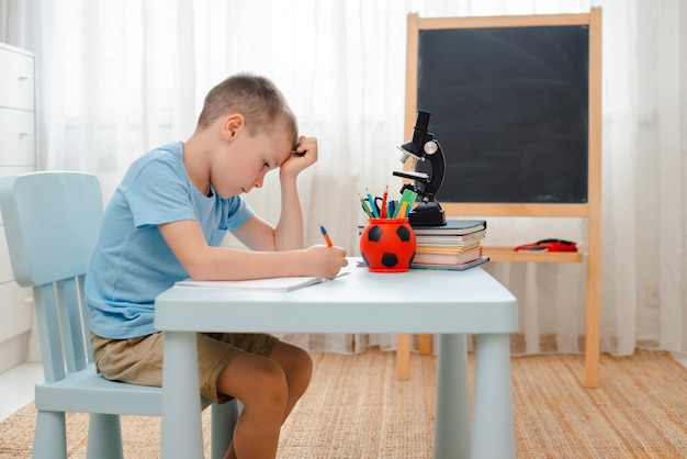 School boy sitting home classroom lying desk filled with books training