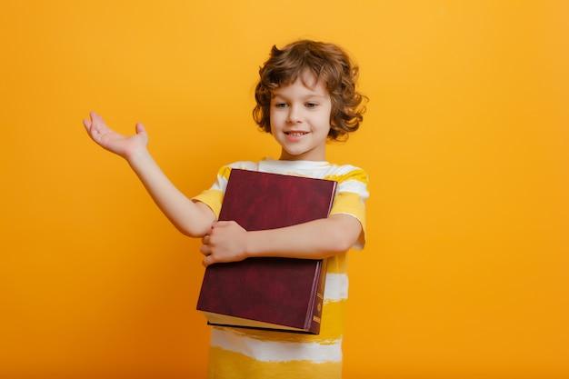 学校の男の子は笑顔、手を挙げて、大きな本を持っています