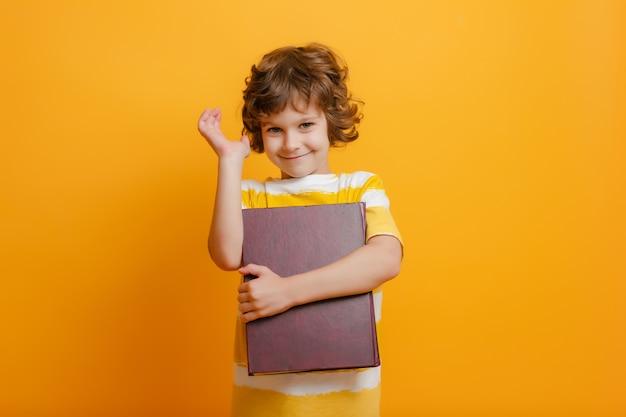 学校の男の子は笑顔、手を挙げて、本を持っています