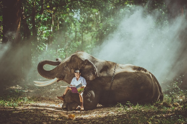 School boy studying in the jungle with his friend elephant
