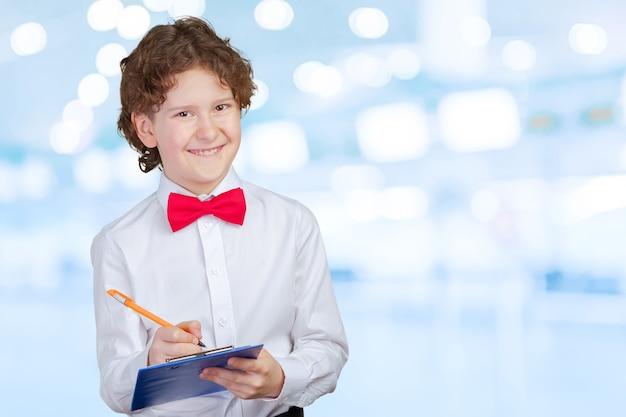 School boy in suit and blank paper sheet in clipboard