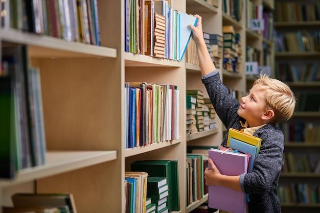 손에 책의 스택과 함께 도서관의 선반에서 책을 복용하는 학교 소년. 아동 두뇌 발달, 읽기 배우기,인지 능력 개념