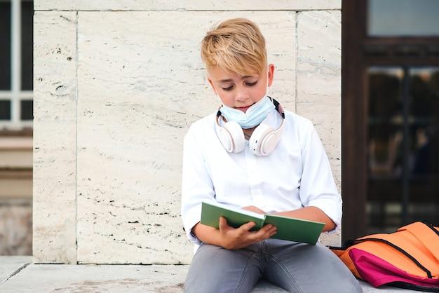 コロナウイルスから保護するためにフェイスマスクを着用している男子生徒。学校のコンセプトに戻る。パンデミック時の教育。レッスン後の防塵マスクで疲れた少年。コロナウイルスと学校生活。