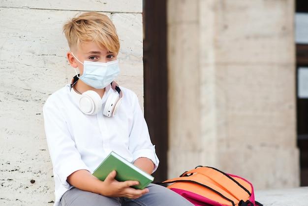 코로나 바이러스로부터 보호하기 위해 얼굴 마스크를 착용하는 학교 소년.