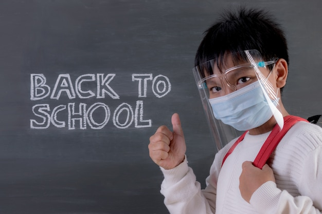 School boy wearing face mask standing against blackboard with text. back to school during covid-19.
