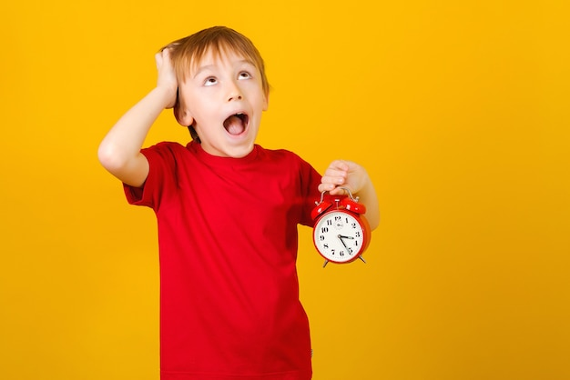 School boy with alarm clock shouting. shocked little student.