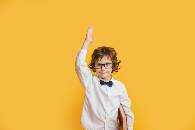 眼鏡の少年は笑顔、手を挙げて、本を保持しています。学校に戻るコンセプト