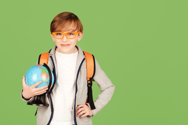School boy with globe isolated over green background. smart boy studying geography. back to school concept. boy wearing glasses and school uniform. education and geography lesson.