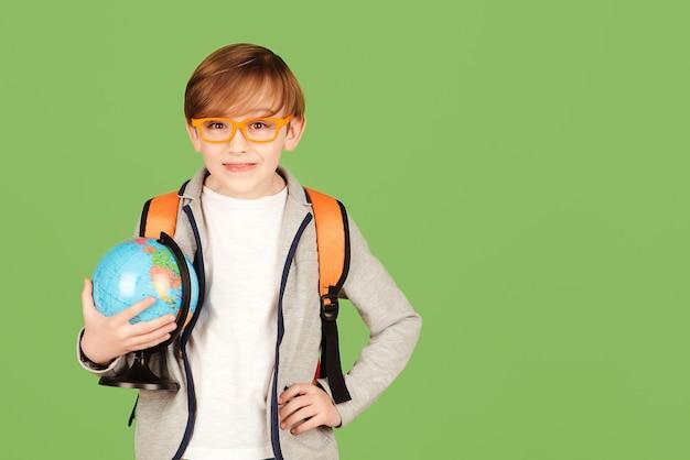 緑の背景で隔離の地球を持つ男子生徒。地理を勉強している賢い少年。学校のコンセプトに戻ります。眼鏡と制服を着た少年。教育と地理のレッスン。