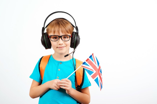 School boy with headphones holding british flag. online english language school. lessons and learning of foreign languages.