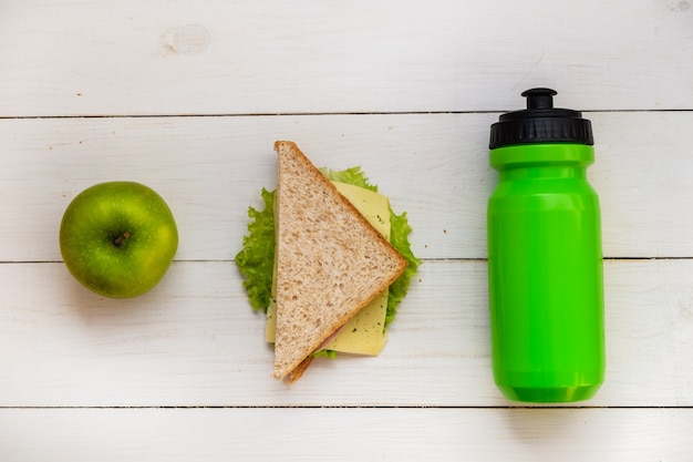 School breakfast on the white table. ham and cheese sandwich, green apple, bottle of water