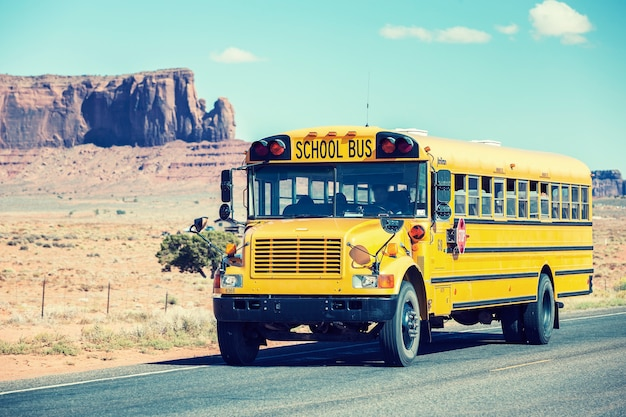 School bus traveling near monument valley