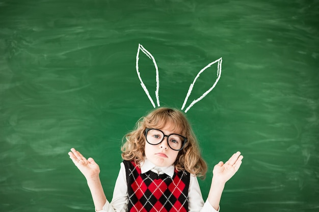 School child in class. sad kid against green blackboard. education concept