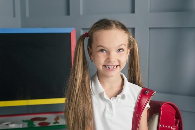 School child in a classroom with blackboard back to school