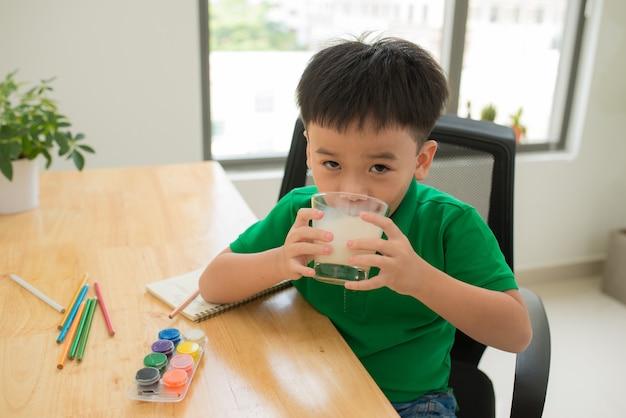 숙제 하 고 우유를 마시는 학교 아이