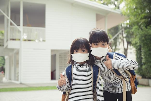 コロナウイルスの発生時にフェイスマスクを着用した小学生少女が学校に戻る