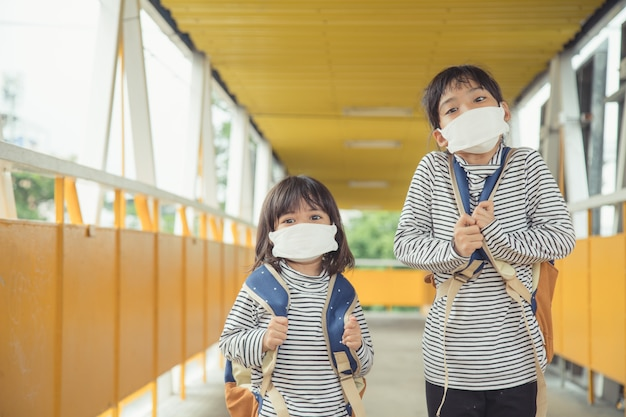 School child wearing a face mask during coronavirus outbreak little girl going back to school