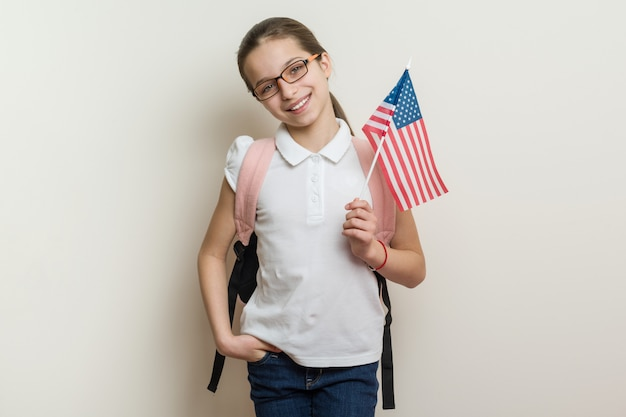 School child with backpack holds the us flag