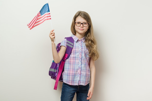 School child with a backpack holds the usa flag