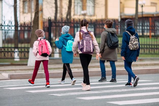 学童は医療用マスクで道を渡ります。子供たちは学校に行きます。