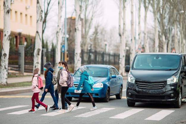 学童は医療用マスクで道路を横断します。子供たちは学校に行きます。