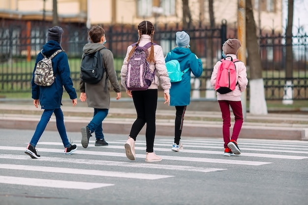 Школьники переходят дорогу в медицинских масках