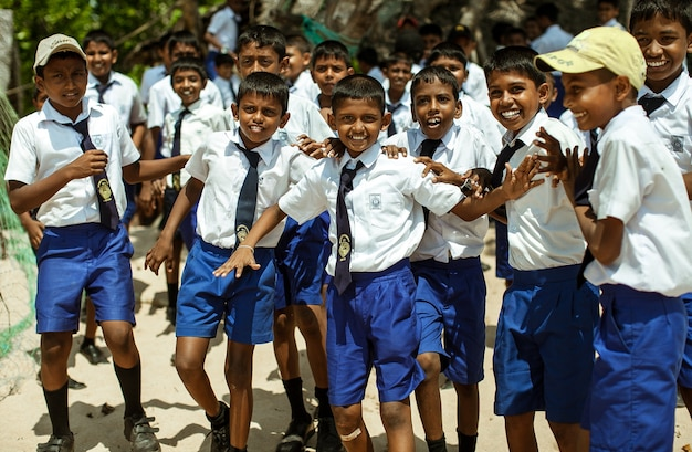 School children dressed in uniform have fun and play in the schoolyard.