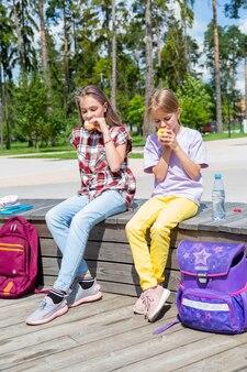 Школьники вместе обедают возле здания девочки в саду делят обед
