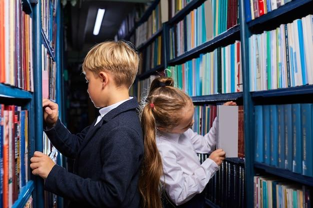 선반 사이에 서있는 책을 선택하는 도서관의 학교 아이들, 학교 준비