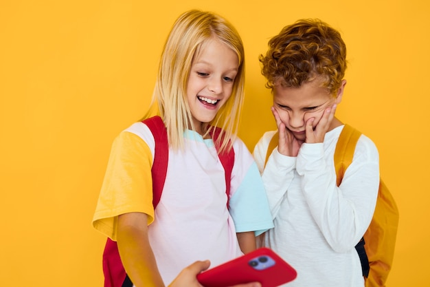School children looking into a smartphone and playing games isolated background. high quality photo