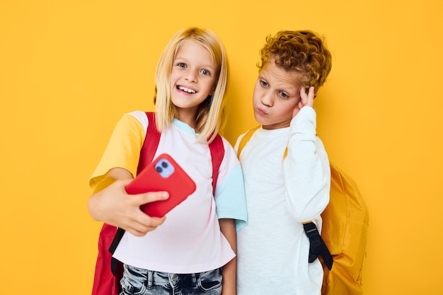 School children looking into a smartphone and playing games yellow background. high quality photo
