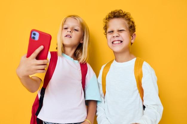 学校の子供たちが子供たちとガジェットの中毒の自分撮りしかめっ面楽しいコンサートに電話をかける