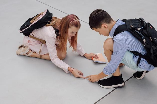 Школьники сидят на бетонном полу и рассматривают жука