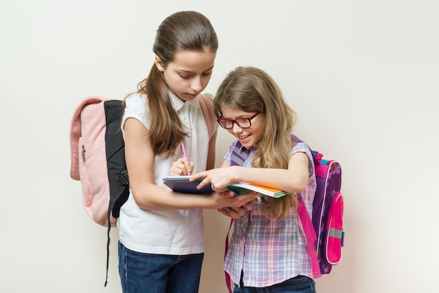 School children, two girls with backpacks write in a notebook.