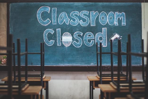 Covid-19 발생으로 인해 학교가 문을 닫고 학교 칠판에 메시지가 게시되었습니다.