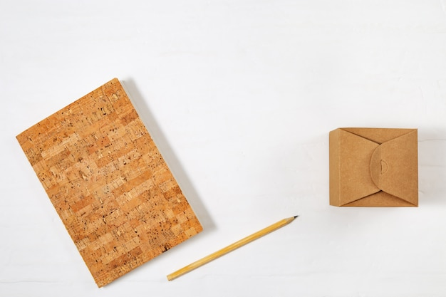 School closed notebook, wooden pencil and craft box on tabletop. top view with copy space, flat lay photography.