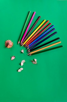 School colored pencils on a paper dark green background. school supplies. flat lay