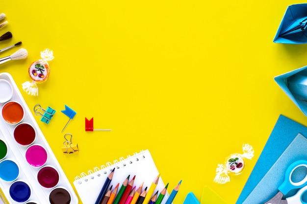 Канцелярские принадлежности школы красочные на желтом фоне с copyspace.