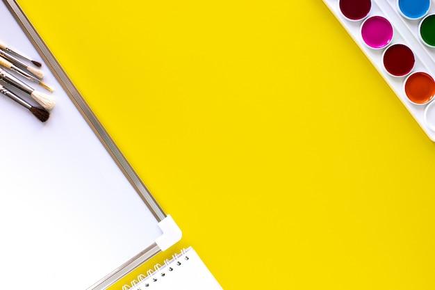 Школа красочные канцелярские товары на желтом фоне с copyspace