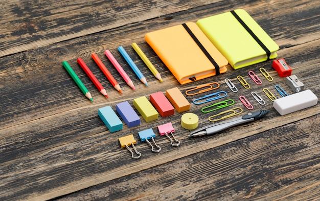 お手本と学校のコンセプト、木製テーブルハイアングルの学用品。