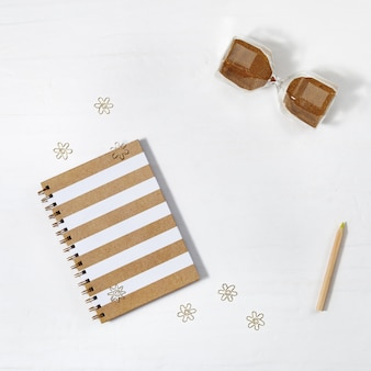 School copybook with metal clips. closed notebook on spring, hourglass and wooden pencil on light work space. back to school concept. top view.